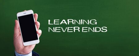 Smart phone in hand front of blackboard and written LEARNING NEVER ENDS