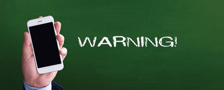 Smart phone in hand front of blackboard and written WARNING! Stock Photo