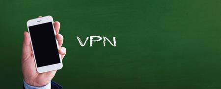 Smart phone in hand front of blackboard and written VPN Stock Photo