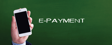 epayment: Smart phone in hand front of blackboard and written E-PAYMENT