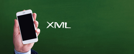 xml: Smart phone in hand front of blackboard and written XML Stock Photo