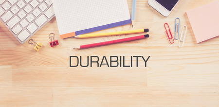 durability: Business Workplace with  DURABILITY Concept on Wooden Background