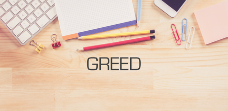 avid: Business Workplace with  GREED Concept on Wooden Background