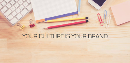 Business Workplace with  YOUR CULTURE IS YOUR BRAND Concept on Wooden Background