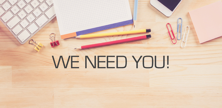 recruit help: Business Workplace with  WE NEED YOU! Concept on Wooden Background