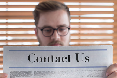 respond: Man reading Contact Us headlined newspaper