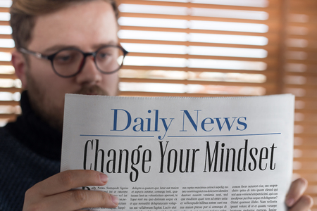 Man reading Change Your Mindset headlined newspaper
