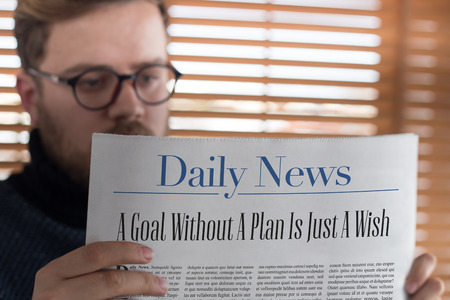 strategic focus: Man reading A Goal Without A Plan Is Just A Wish headlined newspaper