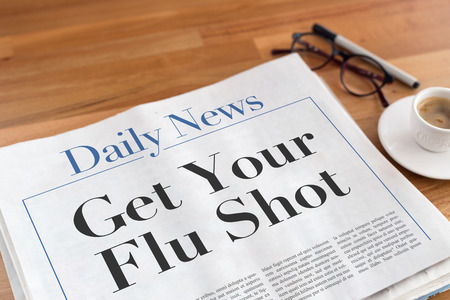 swine flu vaccinations: Get Your Flu Shot headlined newspaper on the table
