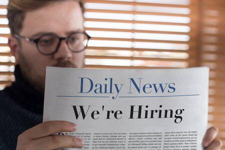 were: Man reading Were Hiring headlined newspaper