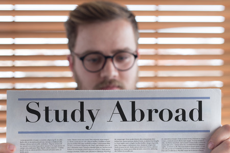 Man reading Study Abroad headlined newspaper