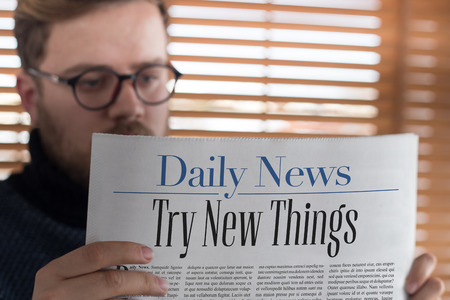 place of employment: Man reading Try New Things headlined newspaper Stock Photo