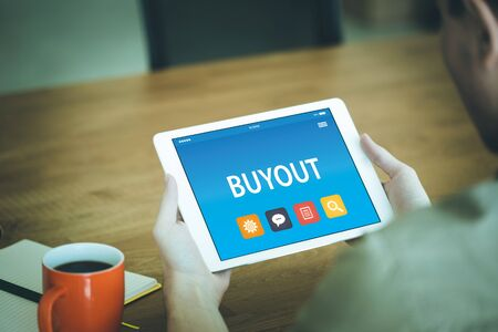 acquiring: BUYOUT CONCEPT ON TABLET PC SCREEN Stock Photo