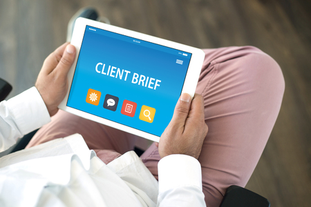 brief: CLIENT BRIEF CONCEPT ON TABLET PC SCREEN Stock Photo