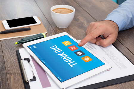 overachiever: THINK BIG CONCEPT ON TABLET PC SCREEN Stock Photo