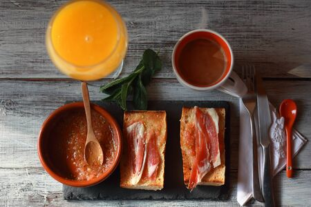 Typical Spanish breakfast, with crushed tomato toast, Iberian ham, orange juice and coffee with milk.