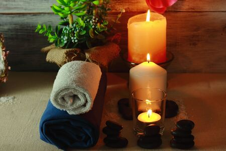 Beautiful spa composition with candles, flowers, jars of mineral salts, oils and other decoration elements