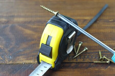screws with Phillips screwdriver and tape measure Foto de archivo