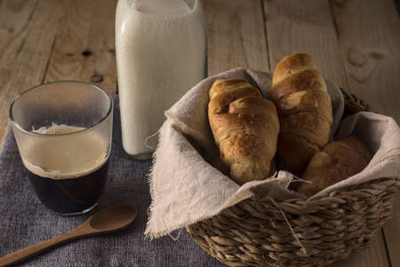 freshly baked croissant in a wicker basket on a table with coffee and milk, ready to take at breakfast or snack 免版税图像