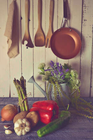 vegetables in a rustic kitchen with white board walls and aged blue countertop