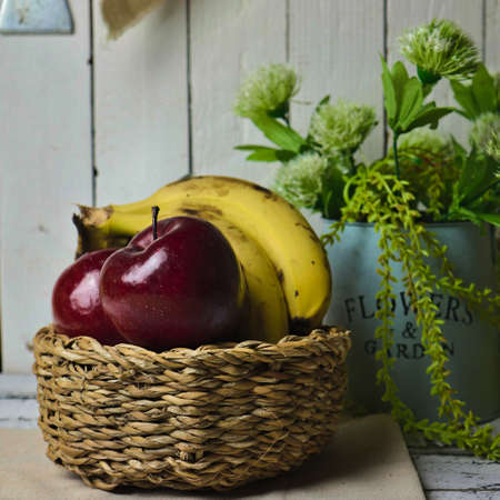 apples and bananas in a basket and a vintage kitchen background