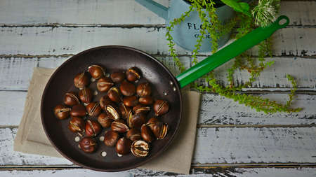 chestnuts cooked over a fire in a pan with holes and a vintage kitchen in the background
