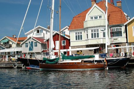 enyoing: Boats docked at a Swedish west coast village with people enyoing the beautiful summer day
