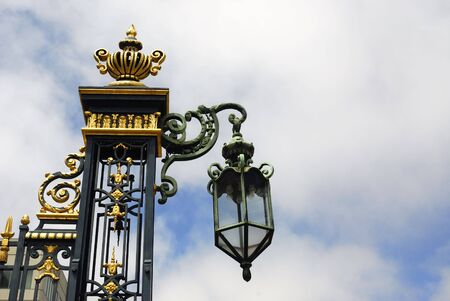 Beautiful lamp and wrought iron work with golden inlays against a dramatic sky Banco de Imagens