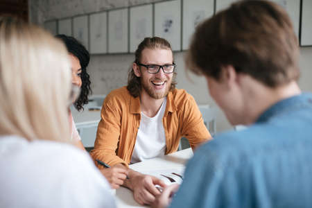 Portrait of young smiling man with blond hair and beard happily looking at friends. Joyful boy in glasses sitting in office and working with friends