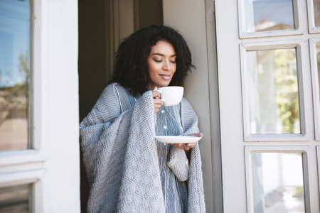 Nice African American girl drinking coffee in restaurant. Young girl standing with cup of coffee and dreamily closed her eyes. Portrait of lady with dark curly hair leaning on door with cup in hands