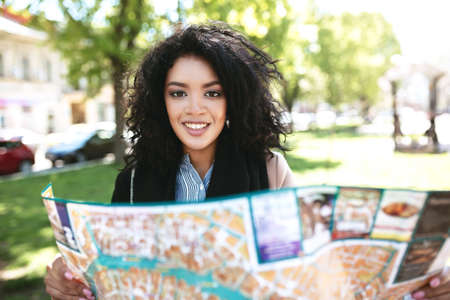 Pretty African American girl joyfully looking in camera with map in hands. Cool girl standing on street and searching right way on map. Portrait of smiling lady with dark curly hair with map in town Stock Photo