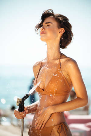 Happy girl in bikini using hose pipe on beach. Portrait of lady in beige swimsuit rinsing beach sand off her body on beach. Young girl dreamily closing her eyes while pouring water from hose on beach Banco de Imagens