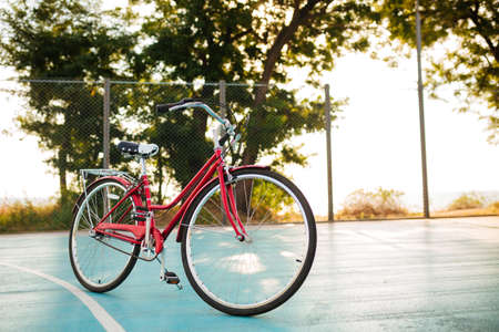 Close up photo of red classic bicycle standing on basketball court in park. Beautiful photo of bicycle