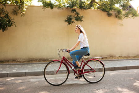 Beautiful girl with blond hair happily riding bicycle. Young lady in jeans and sunglasses on head having fun while riding on red bicycle along city streets