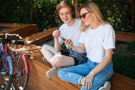 Fröhliches Paar, das auf Bank im Park sitzt und glücklich im Handy mit zwei Fahrrädern in der Nähe schaut. Junger lächelnder Mann und hübsche Dame mit blondem Haar verbringen Zeit zusammen