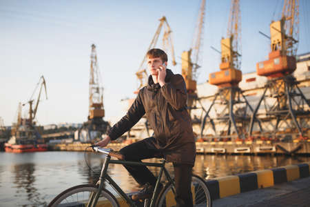 Young man with brown hair standing with bicycle and thoughtfully looking aside while talking on his mobile phone. Cool boy in down jacket on bicycle standing with sea port on background Stock Photo