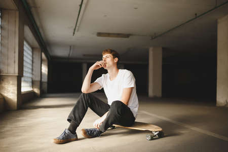 Cool boy with brown hair sitting on skateboard and smoking. Young thoughtful man in white t-shirt sitting and holding cigarette in hand dreamily looking aside Stock Photo