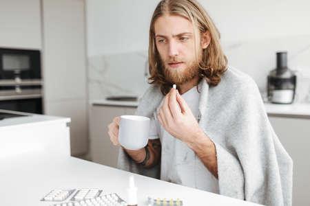 Homme malade assis avec une tasse et des pilules dans les mains dans la cuisine à la maison Banque d'images
