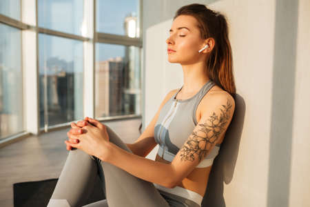 Thoughtful girl sitting on yoga mat listening music in earphones at home over beautiful window 스톡 콘텐츠 - 125595437