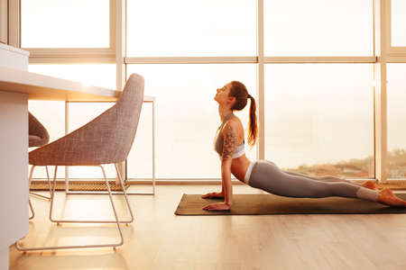 Lady in sporty top and leggings practicing yoga on yoga mat at home with big beautiful windows 스톡 콘텐츠 - 125595438