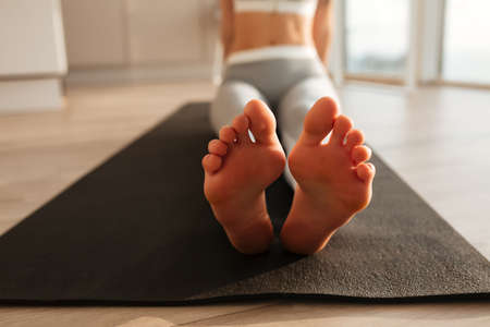 Female feets on yoga mat at home