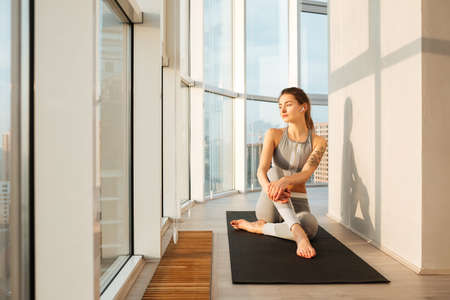 Pretty lady in sporty top and leggings sitting on yoga mat and thoughtfully looking in window 스톡 콘텐츠 - 125595978