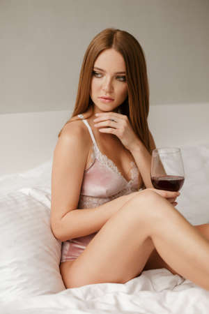 Pretty lady sitting in bed and holding glass of red wine while thoughtfully looking aside