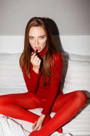 Signora rossa in maglione rosso e calzamaglia seduta a letto usando il rossetto che guarda sognante a porte chiuse