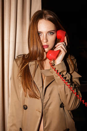 Beautiful lady in trench coat talking on red telephone thoughtfully looking in camera 免版税图像