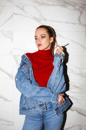Junge schöne Frau in Jeansjacke und Jeans hält Zigarette nachdenklich beiseite