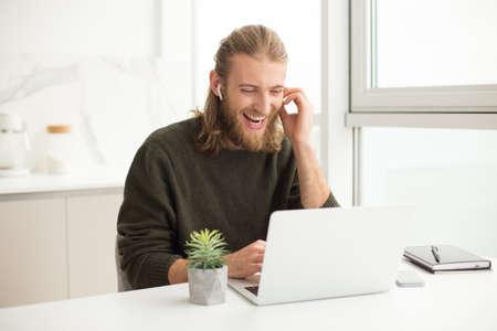 Junger fröhlicher Mann mit Kopfhörern, der am Tisch sitzt und lacht, während er zu Hause im Laptop schaut