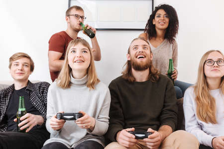 Cheerful friends sitting on sofa and spending playing video games and drinking beer