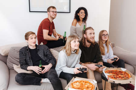 Friends sitting on sofa spending time together playing video games, eating pizza and drinking beer Banque d'images