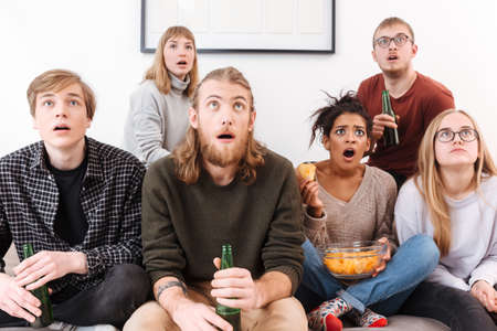 Amazed friends sitting on sofa and watching movie together with chips and beer at home